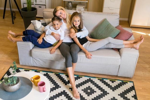 Posibilidad muy remota de madre e hijos sentados en un sofá Foto gratis