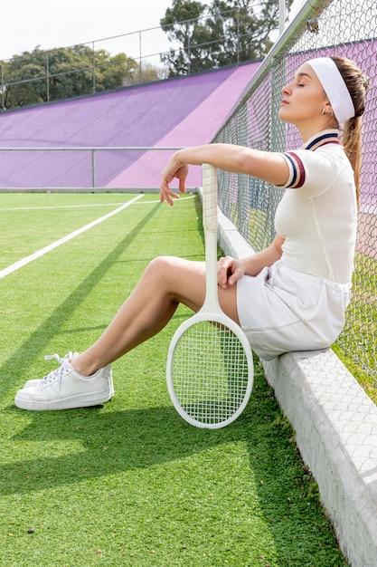 Posibilidad muy remota de la mujer del tenis de lado en un campo de tenis Foto gratis
