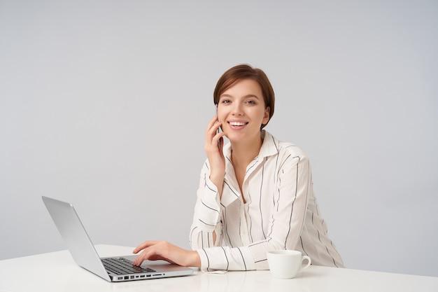 Positiva joven encantadora morena de ojos marrones mujer de negocios haciendo llamadas con su teléfono inteligente y manteniendo la mano en el teclado de la computadora portátil mientras mira alegremente Foto gratis