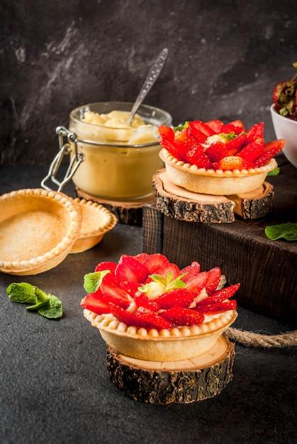 Postre de verano y primavera. tartas caseras de tartaletas con crema pastelera y fresas Foto Premium
