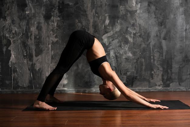 Postura de yoga de mujer de tiro completo en estera Foto gratis