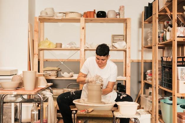Potter femenino joven que forma un borde en el jarro en el taller Foto gratis