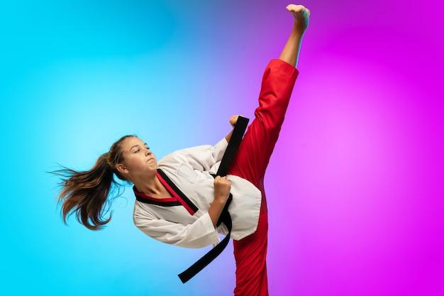 Práctica. karate, taekwondo chica con cinturón negro Foto gratis