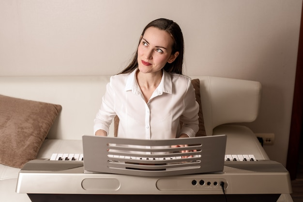 Practica tocando el sintetizador, retrato frontal de una mujer en un piano electrónico Foto Premium