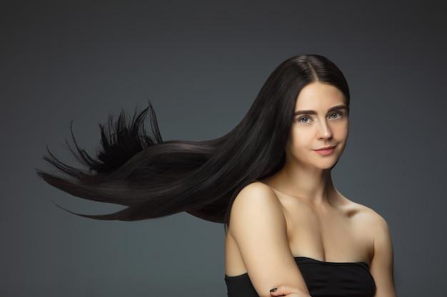 Preciosa modelo con cabello castaño largo, liso y volador Foto gratis