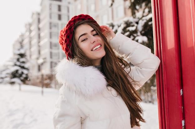 Preciosa modelo femenina con peinado recto posando en la calle nevada de buen humor. foto exterior de mujer pálida alegre con gorro rojo tejido divirtiéndose durante el invierno Foto gratis