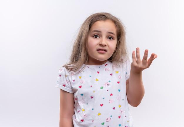 Preocupada niña de la escuela con camiseta blanca levantando las manos sobre la pared blanca aislada Foto gratis