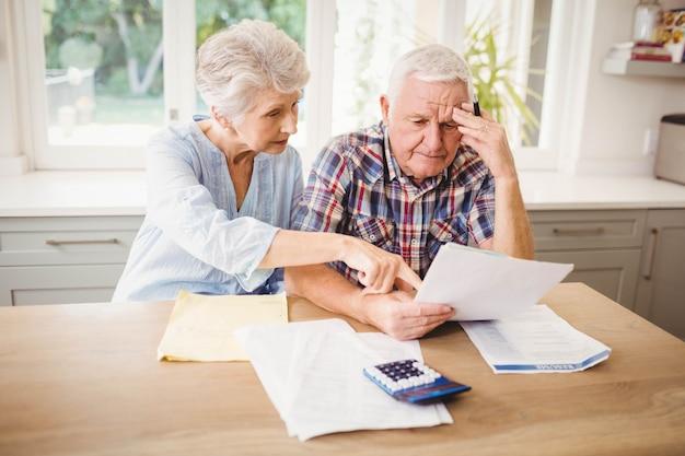 Preocupado pareja senior revisando sus facturas en casa Foto Premium