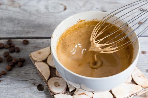 Preparación de café dalgona en un bol sobre una mesa de madera Foto Premium