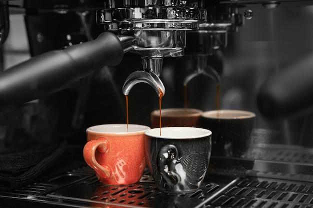 Preparación de café con máquina y tazas. Foto gratis