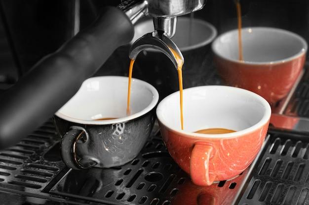 Preparación de café con tazas y máquina. Foto gratis