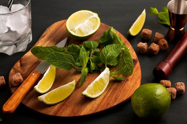 Preparación de cóctel mojito. utensilios de barra e ingredientes menta, lima, hielo y azúcar de caña. vista superior con espacio de copia Foto Premium