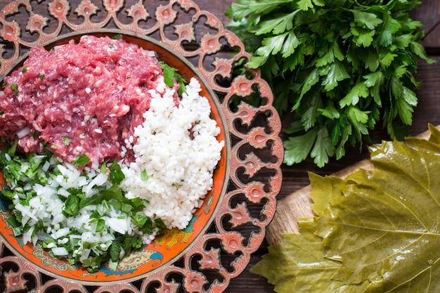 Preparar hojas de parra rellenas con arroz y carne, o dolma tradicional. vista superior Foto Premium