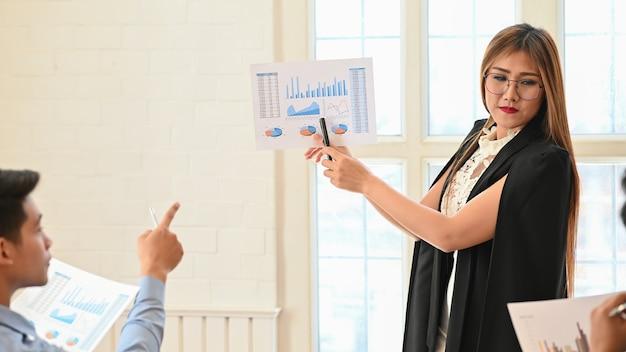 Presentación de la empresaria con papel gráfico estático de finanzas en la sala de reuniones. Foto Premium