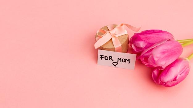 Presente caja con lazo cerca de nota y flores. Foto gratis