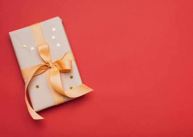 Presente cubierto de estrellas doradas con espacio de copia Foto gratis