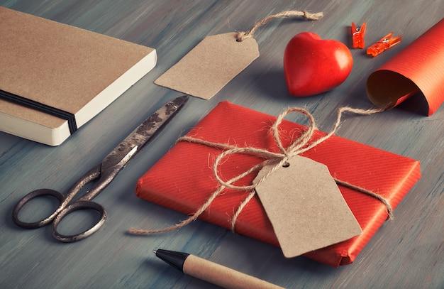 Presente empaquetado, papel de regalo, etiquetas y decoraciones en la mesa de madera rústica Foto Premium