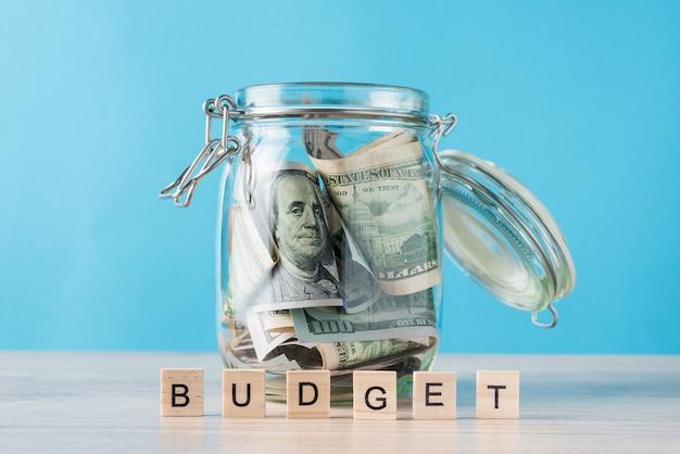 Presupuesto de la palabra y billetes de dólares en frasco de vidrio en azul Foto Premium