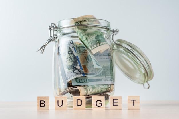 Presupuesto de word y billetes de un dólar en frasco de vidrio Foto Premium