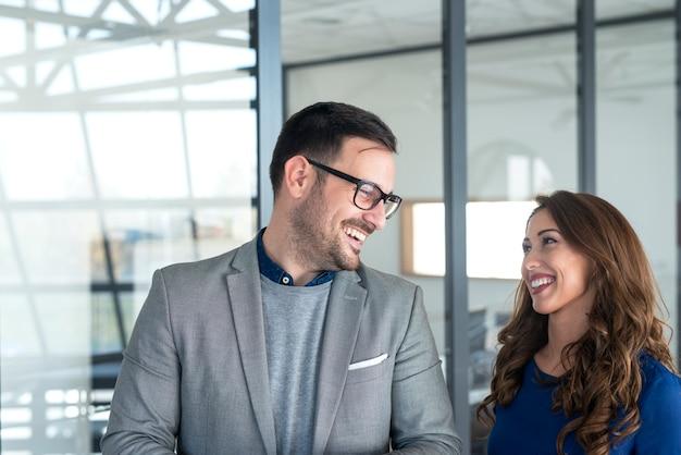 Pretty empresaria y gerente mirando el uno al otro y sonriendo. Foto Premium