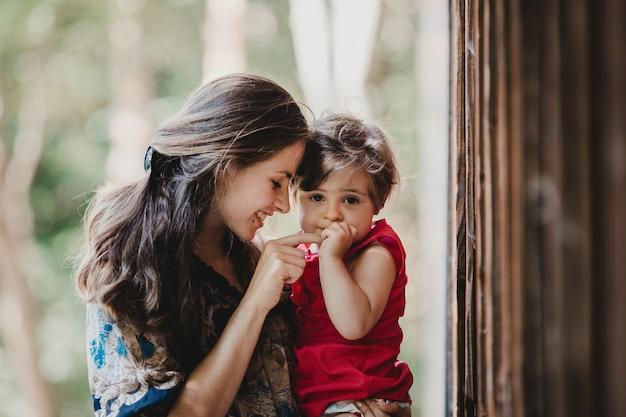 Pretty little child tiene el dedo de la madre sentado en sus brazos Foto gratis