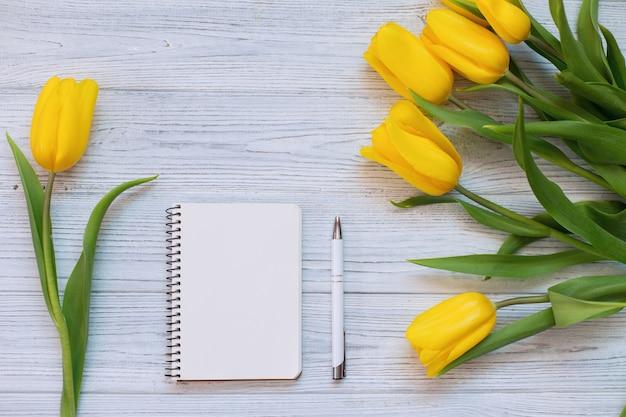 Primavera tulipanes amarillos, cuaderno en blanco y bolígrafo. vista plana, vista superior. Foto Premium