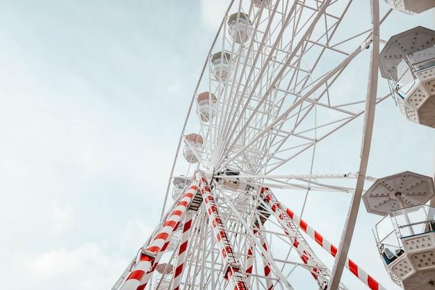 Primer ángulo bajo del carrusel de la noria con rayas rojas y blancas en él Foto gratis