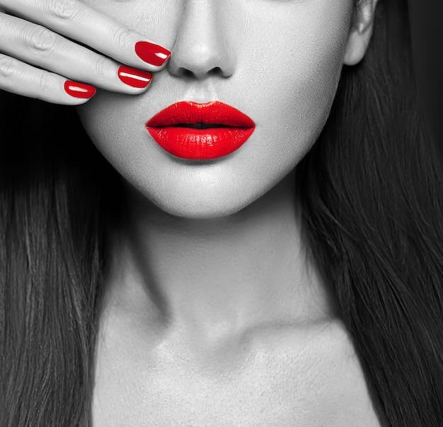 Primer atractivo rosado de los labios y de las uñas. boca abierta. manicure y maquillaje. Foto gratis