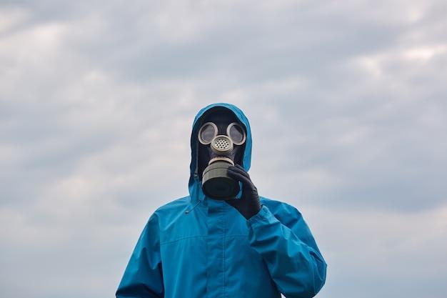 Primer científico químico o ecologista posando al aire libre, viste uniforme azul y respirador, el científico explora los alrededores y pide proteger nuestro medio ambiente. concepto de ecología. Foto gratis