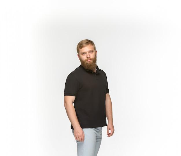 Primer del cuerpo del hombre joven en la camiseta negra vacía aislada en el fondo blanco. simulacros de concepto de diseño Foto gratis