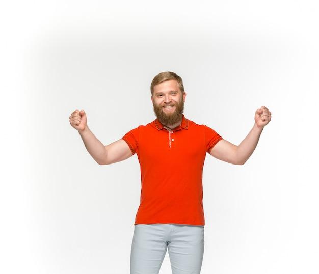 Primer del cuerpo del hombre joven en la camiseta roja vacía aislada en el fondo blanco. simulacros de concepto de diseño Foto gratis