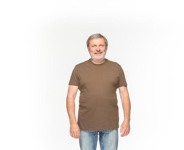 Primer del cuerpo del hombre mayor en la camiseta marrón vacía aislada en el fondo blanco. simulacros de concepto de diseño Foto gratis