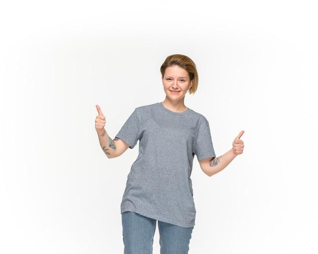 Primer del cuerpo de la mujer joven en la camiseta gris vacía aislada en el espacio blanco. simulacros de concepto de diseño Foto gratis