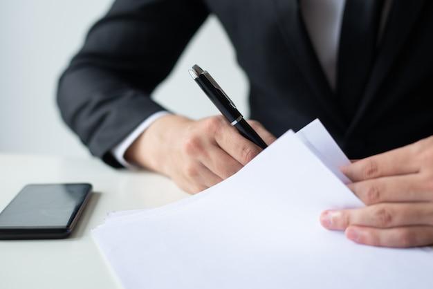 Primer del documento de firma del hombre de negocios en el escritorio de oficina Foto gratis
