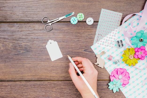 Primer de la escritura de la mujer en la etiqueta blanca con los botones; flores; tijera y artículos decorativos en mesa de madera. Foto gratis