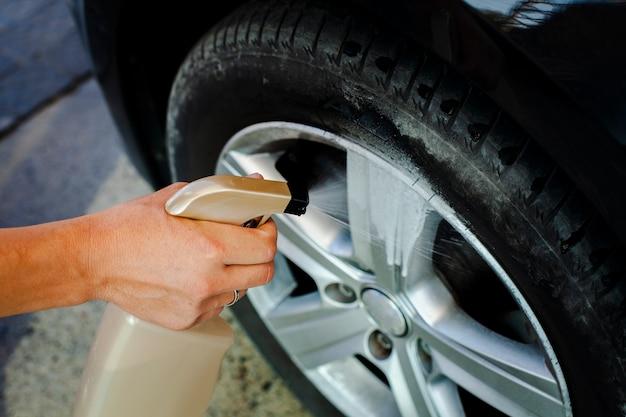 Primer hombre mano rociando una rueda de coche Foto Premium