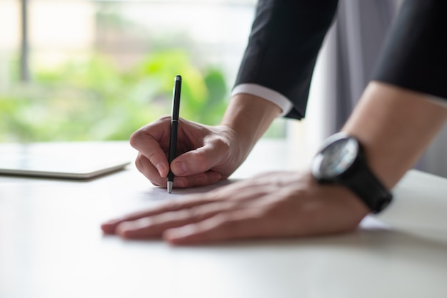 Primer del hombre de negocios que escribe en la hoja de papel en el escritorio Foto gratis