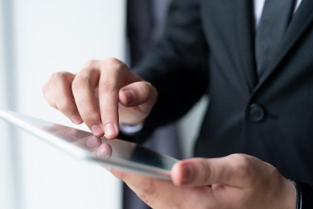Primer del hombre de negocios que sostiene y que usa la tableta Foto gratis