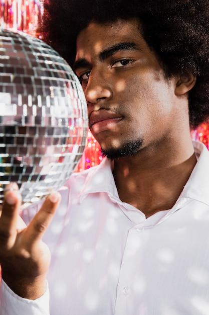 Primer hombre sosteniendo una bola de discoteca Foto gratis