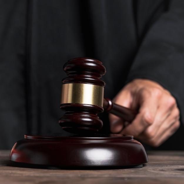 Primer juez en bata golpeando martillo Foto gratis
