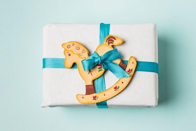 El primer de un juguete de la caja y del caballo mecedora de regalo ató con la cinta azul en fondo Foto gratis