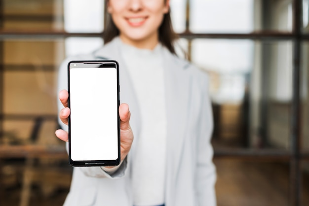 Primer de la mano de la empresaria que muestra el teléfono móvil de la pantalla en blanco en la oficina Foto gratis