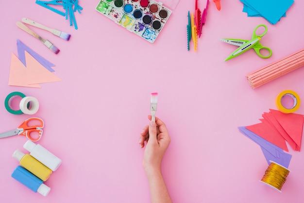Primer de la mano de la mujer que sostiene el pincel con la paleta de colores del agua; cepillo de pintura; papel; tijera sobre fondo rosa Foto gratis