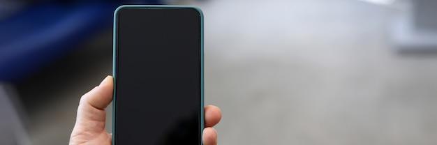 Primer de la mano de las personas que sostiene smartphone moderno con la pantalla negra. estilo de maqueta copie el espacio en el lado derecho. dispositivo para la diversión o el trabajo. concepto de tecnología y entretenimiento Foto Premium