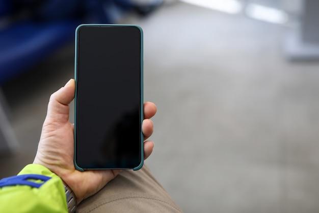 Primer de la mano de las personas que sostiene smartphone moderno con la pantalla negra. Foto Premium