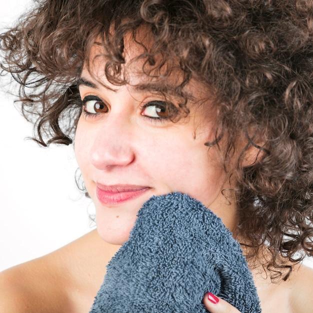 El primer de la mujer joven hermosa limpia la cara con la toalla Foto gratis