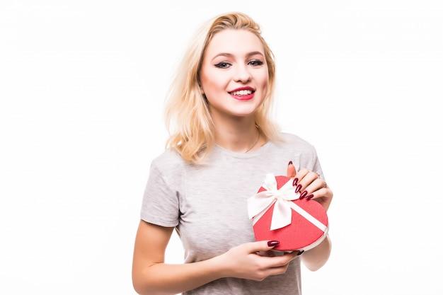 Primer de la mujer sonriente del blondie que sostiene la caja de regalo en forma de corazón Foto gratis