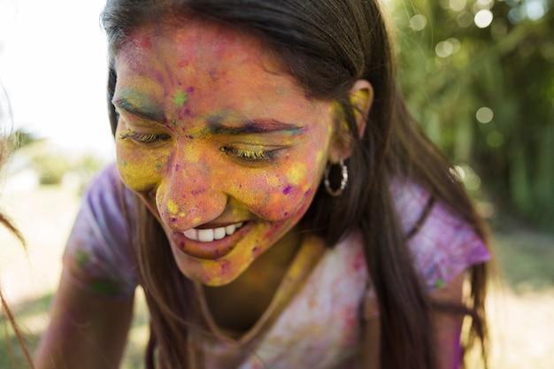 El primer de la mujer sonriente cubrió su cara con color del holi Foto gratis