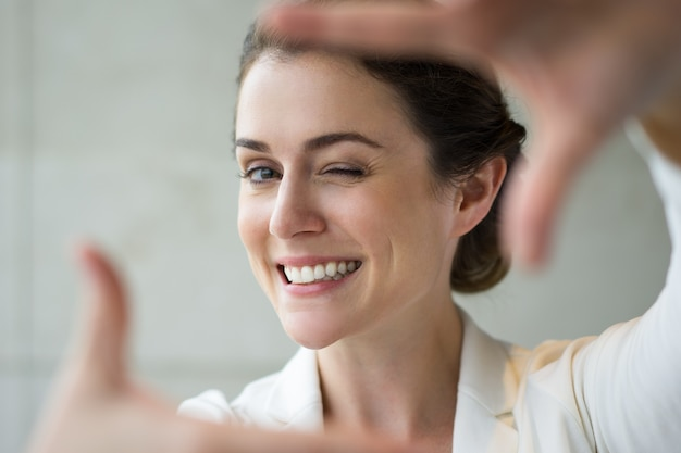Primer de la mujer sonriente que hace gesto del marco Foto gratis