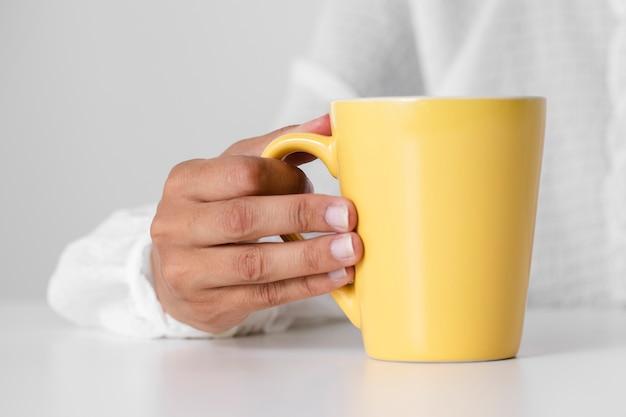 Primer niño sosteniendo una taza amarilla Foto gratis